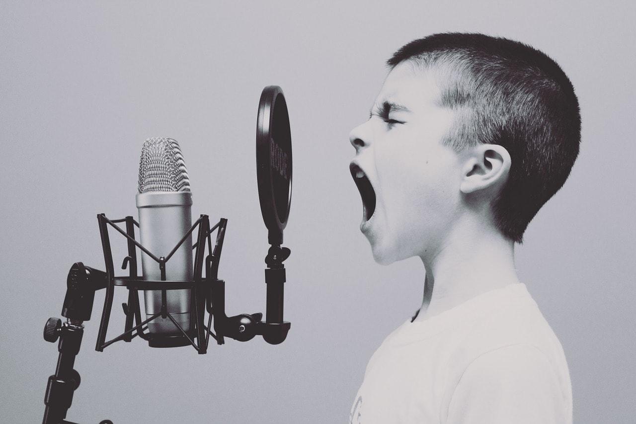 niño gritando a un micrófono Servicios Médicos de Logopedia